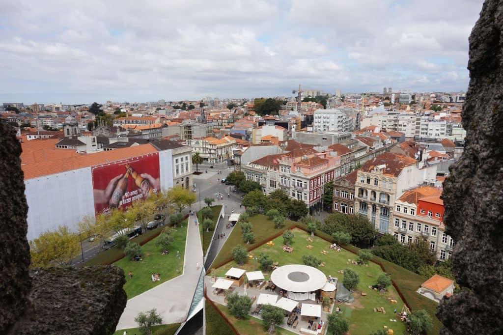 Dole náměstí Praça de Lisboa s garden barem a kavárnami a obchody v přízemí. Ve středu obrázku je vidět další magnet Porta - známá knihovna Livraria Lello & Irmão